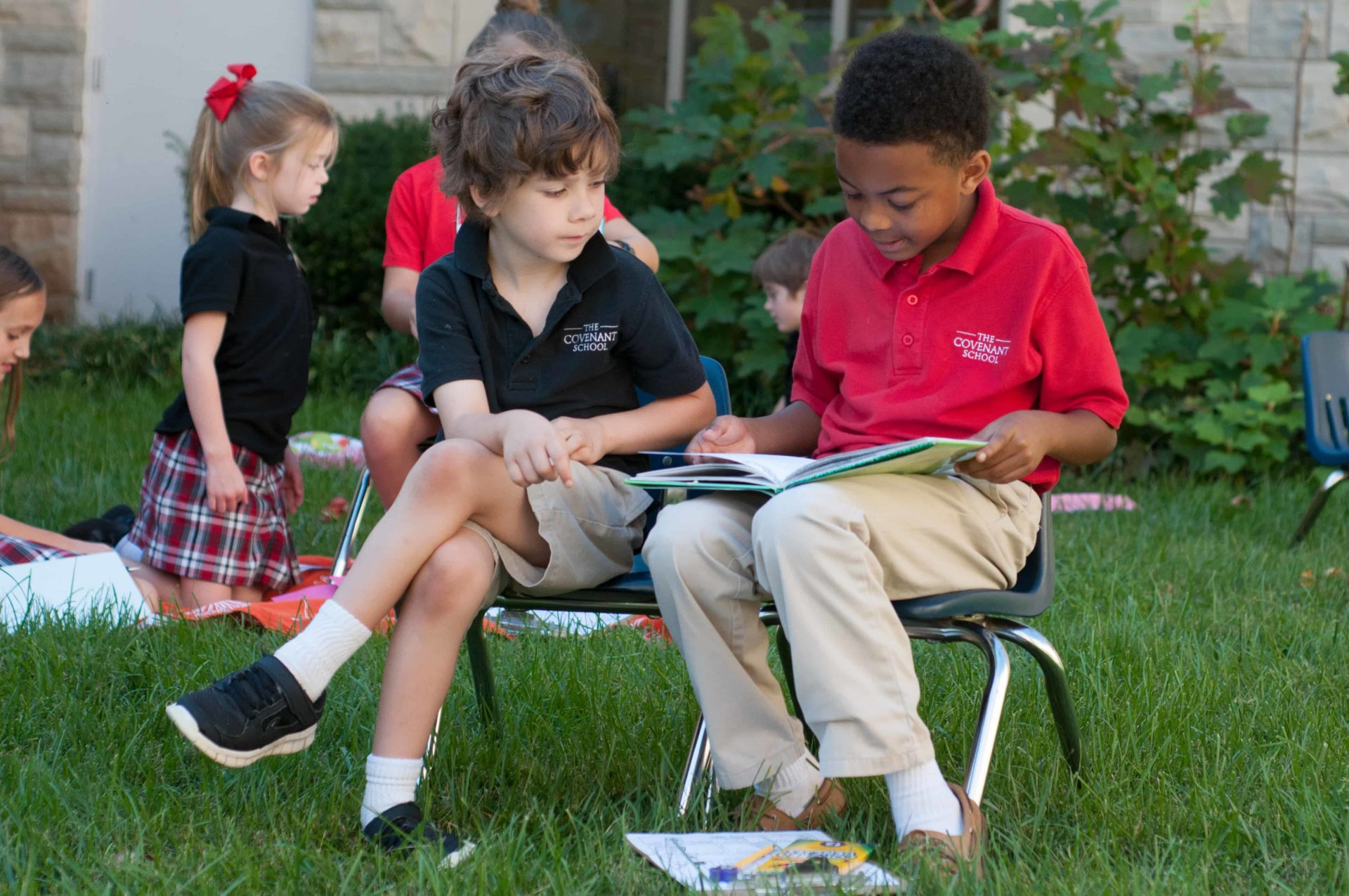 Students outside reading a book